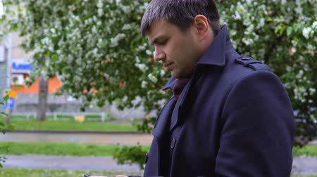 expectativa : A man in a black coat with a mobile phone in his hands is standing and looking around. In the background there are blooming apple trees and an urban landscape.