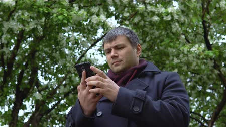 black cab : A man in a black coat stands against the background of blooming apple trees and uses a mobile phone.