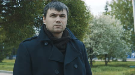 фон : A man in a black coat stands against the backdrop of a cityscape and looks around.
