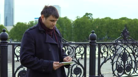 using stylus : A man in a black coat is standing next to the city embankment and uses a tablet.