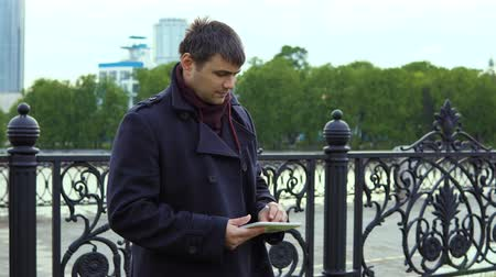 businessmen : A man in a black coat is standing next to the city embankment and uses a tablet.