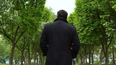 költő : A young man in a black coat walks along the alley of blossoming apple trees in the park. Stock mozgókép