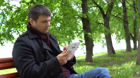 linkerhand : A man in a black coat sits on a bench in the city park and works with a stylus on the tablet. Stockvideo