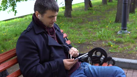 using stylus : A man in a black coat sits on a bench in a city park, listens to music and works with a stylus on a tablet.
