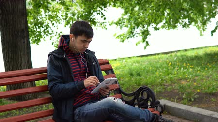 mobile music : A young man sits on a bench in a city park, listens to music and works with a stylus on a tablet.