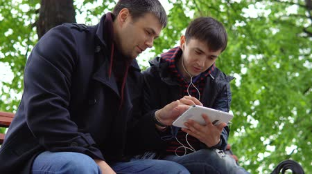 using stylus : Two young people sit in a city park on a bench, look at the tablet, smile and talk. Stock Footage