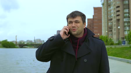 borotválatlan : A man in a black coat is talking on a mobile phone against the background of a city embankment and multi-storey buildings. Stock mozgókép