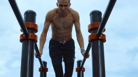 paralelo : A lean and muscular guy trains on workout bars. In the background a cloudy sky.
