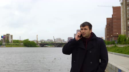 göz alıcı : A man in a black coat is talking on a mobile phone against the background of a city embankment and multi-storey buildings. Stok Video