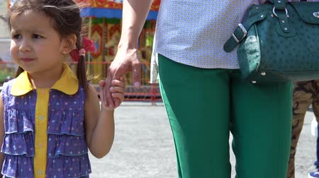 карусель : A dissatisfied little girl goes with her mother by the hand in the amusement park.