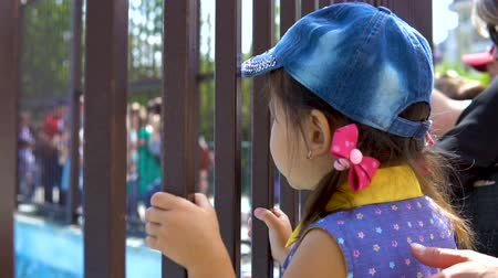 know : A little girl looks through the metal bars of the cage in the zoo. Next to her is her mother.