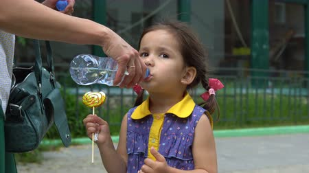 conserva : A little girl drinks from a plastic bottle, which her mother keeps. In the hand of the girl is a large candy on a stick.