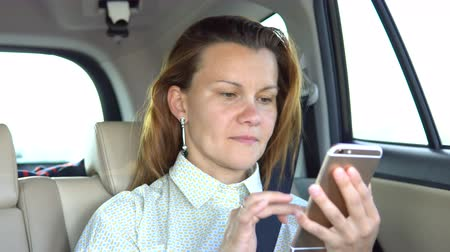 somente para adultos : A young woman is sitting in the back seat of a car and is using a mobile phone.