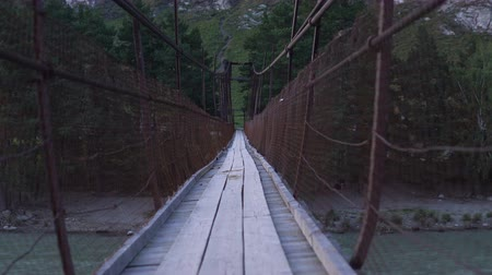 corda : A fictional character is walking along a swinging suspension bridge that hangs over the river.
