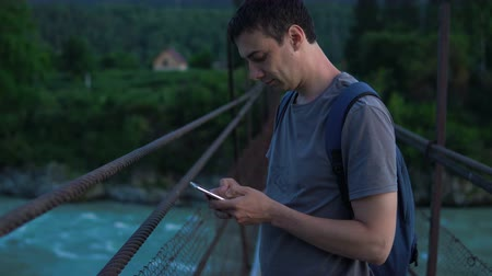 中断 : A lonely tourist stands on a suspension bridge over a river and uses his mobile phone. 動画素材