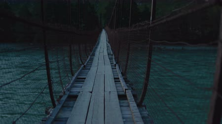 suspensão : A fictional character is walking along a swinging suspension bridge that hangs over the river.