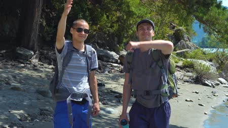 communion : Two tourists with backpacks smile and wave their arms to other tourists, greeting them. In the background a river, forest, mountains, blue sky. Stock Footage