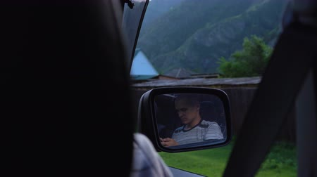 driveway : View from the rear seat of a car on a young man reflected in a rear-view mirror. The man is using a mobile phone. Mountain countryside.
