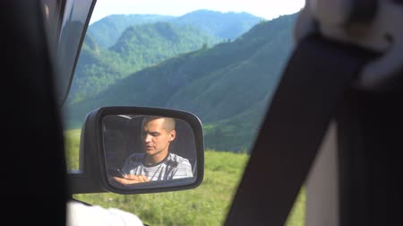 indicação : View from the rear seat of a car on a young man reflected in a rear-view mirror. The man is using a mobile phone. Mountain countryside.