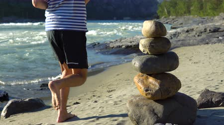 equilibrium : A pyramid of stones stands on the sandy shore of a mountain river. A barefoot young man runs past her.