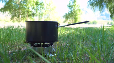 kuchenka : Cooking in the forest on a gas burner. The tourist puts the salt in boiling water.