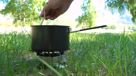 кемпинг : Cooking in the forest on a gas burner. The tourist puts the salt in boiling water.