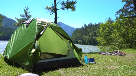harcerz : A green tent of the traveler stands on the bank of a mountain river next to a place for a campfire.