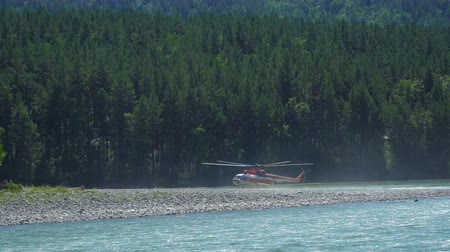 protects : The helicopter Mil Mi-8, which protects the forest from fires, stands on the bank of a mountain river.