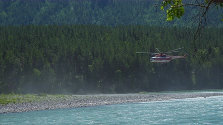 mi : The helicopter Mil Mi-8, which protects the forest from fires, takes off from the shore of a mountain river. Stock Footage