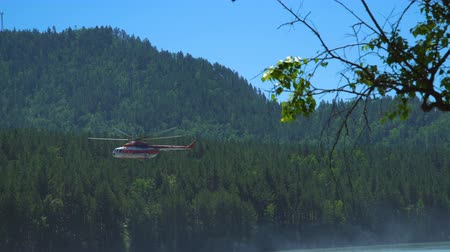 protects : The helicopter Mil Mi-8, which protects the forest from fires, takes off from the shore of a mountain river. Stock Footage