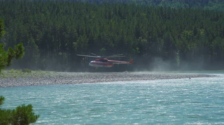 protects : Helicopter Mil mi-8, which protects the forest from fires, lands on the shore of a mountain river.