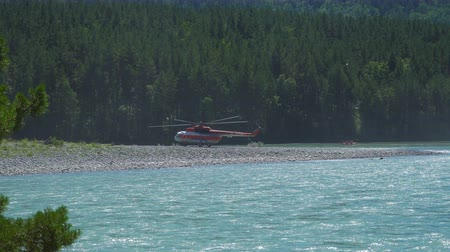 винты : The Mil Mi-8 helicopter, which protects the forest from fires, standing on the bank of a mountain river, is preparing for take-off. A catamaran swims past with a group of people. Стоковые видеозаписи
