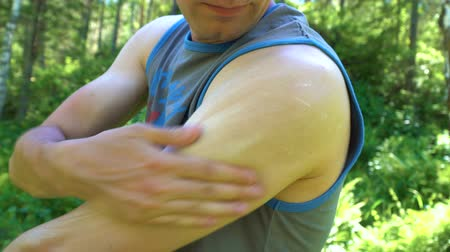 sunblock : The young man uses a protective cream of white color from mosquitoes and other insects. In the background a dense forest. Stock Footage