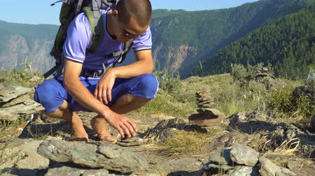 barefooted : A barefooted tourist with a backpack on his back makes a pyramid of stones in the mountains. Stock Footage