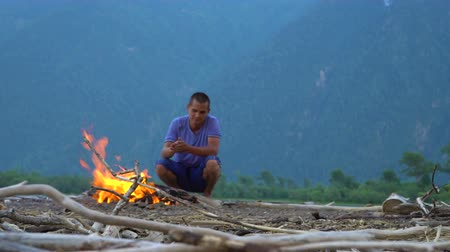 driftwood : The young man is warming himself by the fire on a sandy beach strewn with dry branches and logs. Stock Footage