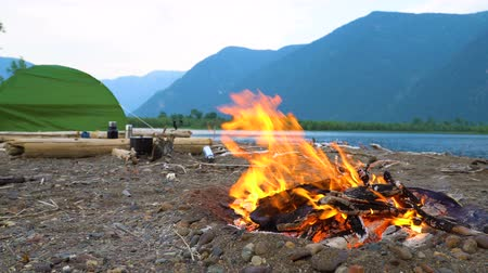 voluntário : A fire burns on the shore of a mountain lake in a tourist camp.
