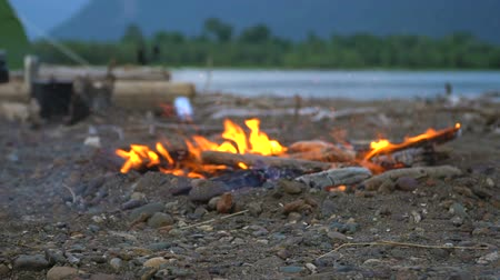 cazo : A campfire burns on the shore of a mountain lake in a tourist camp. The tourist throws wood into the fire.