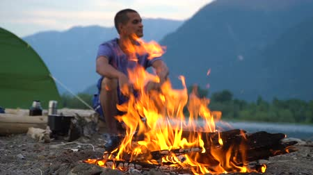 voluntário : A tourist sits by the fire on the shore of a mountain lake in a tourist camp. Evening time.