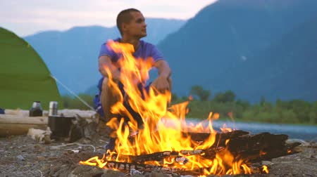 valley of fire : A tourist sits by the fire on the shore of a mountain lake in a tourist camp. Evening time.