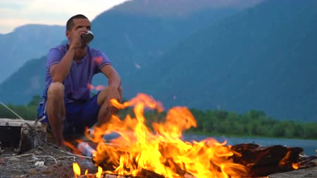 scout : The tourist sits by the fire and drinks tea on the shore of a mountain lake in a tourist camp. Evening time.