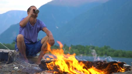 sand bank : The tourist sits by the fire and drinks tea on the shore of a mountain lake in a tourist camp. Evening time.