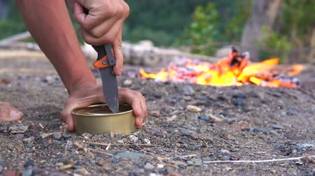 konserve : The traveler opens the can with a knife, being on the sandy shore of the lake next to the fire.