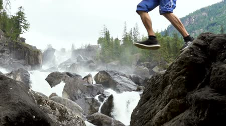 precipizio : A young traveler is jumping against a cascading mountain waterfall.