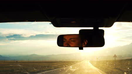 linha do horizonte : A young man drives a car in the countryside in the mountains. Reflection of face in the rearview mirror of the auto. Sunset time.