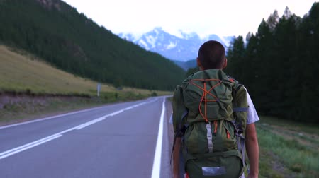 маркировка : A tourist hitchhiker walks along the asphalt road with a backpack on his shoulders. Ahead is a snowy peak of the mountain. Стоковые видеозаписи