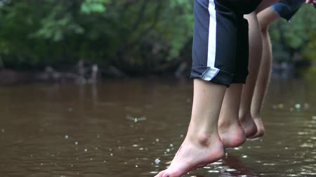 dangle : Teens relaxes by the river sitting on the edge of a wooden bridge, swing ones feet near the water surface. Evening time. Stock Footage