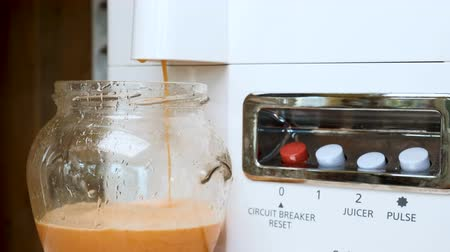 squeezer : Preparation of carrot juice in a juicer. Fast motion. The concept of a healthy diet and a healthy lifestyle.