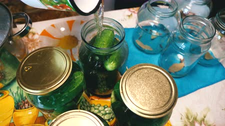 konserve : Preparation of pickled, semi-pickled, low-salt cucumbers. The housewife pours hot marinade into a glass jar with cucumbers and spices.