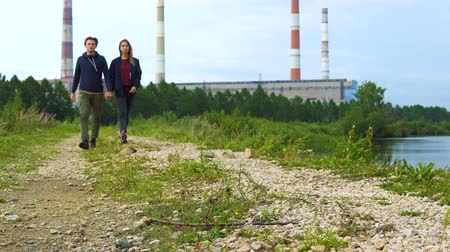 pedregoso : A young man and a girl are walking along a stony path along the river. In the background, a hydroelectric power station and a cloudy sky.