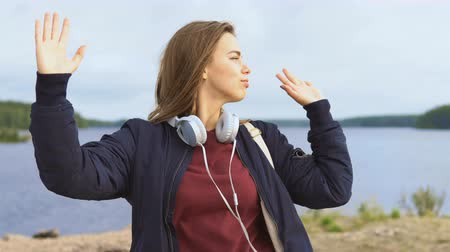 enjoys : A teenage girl dances and enjoys life on the river bank. She wears headphones and casual clothes. Stock Footage
